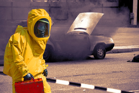 road conditions: Crashed car and man with briefcase in protective hazmat suit Stock Photo