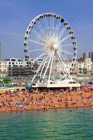 beachfront: BRIGHTON -JULY 14.2013 - View the golden sand of Brighton beachfront to the ferris wheel and amusement park with groups of people on the beach on July 14, 2013
