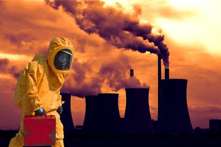 hazmat: View of smoking coal power plant at sunset and men in protective hazmat suit