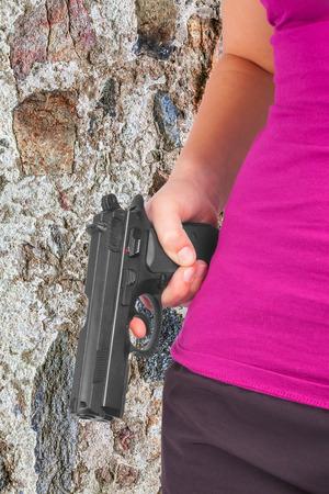 maffia: Woman holding gun in hand against a stone wall Stock Photo