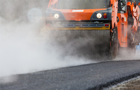heavy equipment operator: Road roller flattening new asphalt