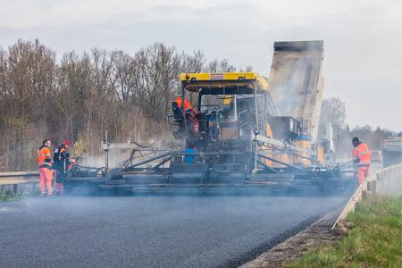 vibration machine: CZECH REPUBLIC, PLZEN, APRIL 10, 2016: Worker operating asphalt paver machine During road construction and repairing works Editorial