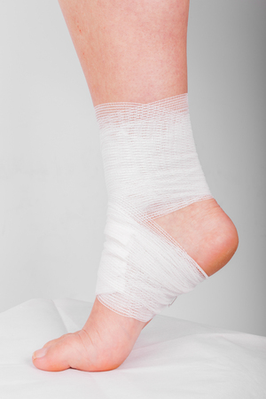 sprained joint: Injured ankle with bandage on a gray background Stock Photo