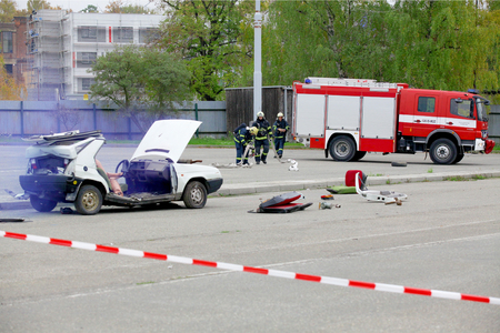 salvaging: CZECH REPUBLIC, PLZEN, SEPTEMBER 30, 2015: Simulation of a car accident. Firefighters and Rescuers are helping Injured person by the car accident.