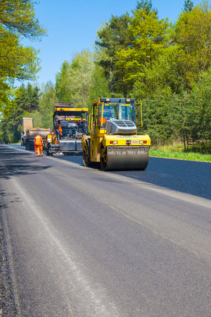 heavy equipment operator: CZECH REPUBLIC, PLZEN, MAY 7, 2016: Asphalt spreading machine and vibration roller at pavement road works.