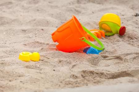 Set of color plastic toys on a sand