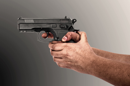 Hand holding a gun isolated on gray background