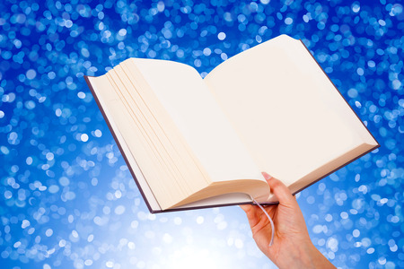 Female hand holding a book isolated on blue background