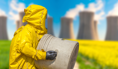 View of coal power plant smoking and men in protective hazmat suit Stock Photo