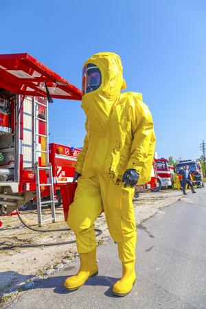 Mens in gele beschermende hazmatkostuum en brandvrachtwagens