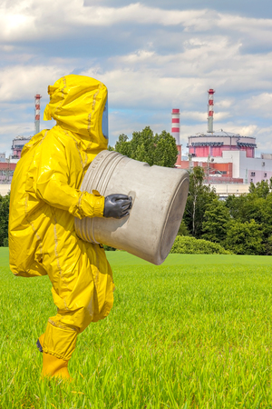Man in yellow protective hazmat suit, factory in background