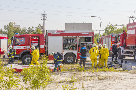CZECH REPUBLIC, Dobrani, JUNE 4, 2014: Mans in protective hazmat suit and fire trucks