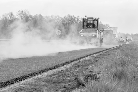 CZECH REPUBLIC, PLZE?, 7 MAY, 2016: Asphalt spreading machine and vibration roller at work road pavement. Black and white photo.