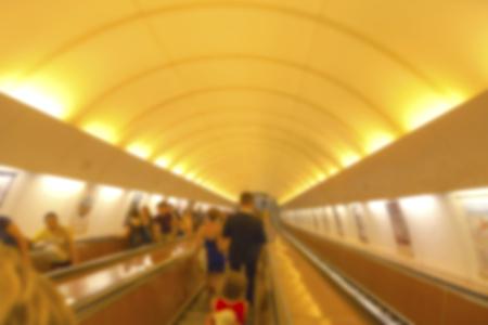 People in motion in escalators at metro