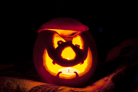 The carved face of a pumpkin glowing on Halloween Stock Photo
