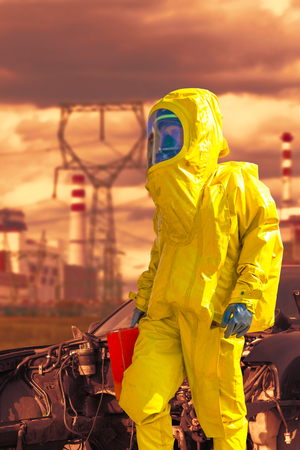 View of a nuclear power plant and a firefighter in a chemical protective hazmat suit next to the demaged car.