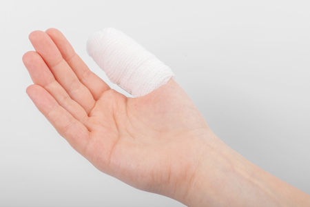 Injured finger with bandage on white background