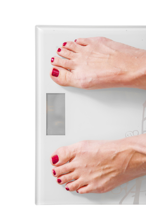 Female feet on personal scales - obesity and diet concept