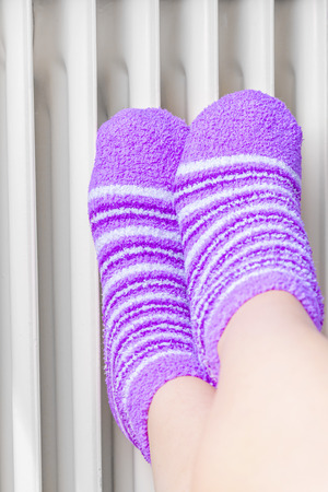 Woman in bright winter socks warm their feet near the radiator.