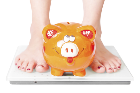 Female feet on body scales and orange pig-obesity and diet concept