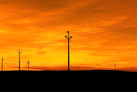 Electricity pylons at sunset sky