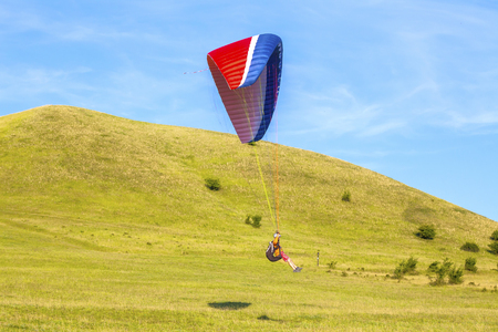 Paraglider over the green valley Stock Photo