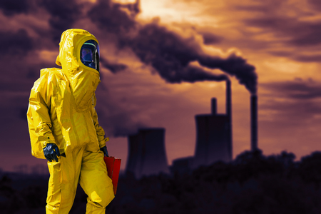 View of a smoking coal power plant and a man in a protective hazmat suit