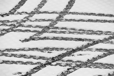 Tracks of car tires in thin layer of first snow Stock Photo