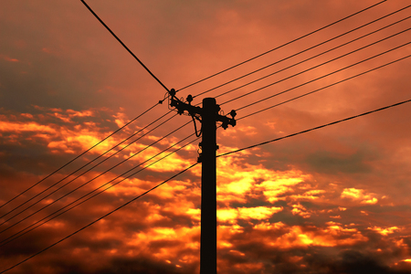Electric power pylon and wires at sunset.