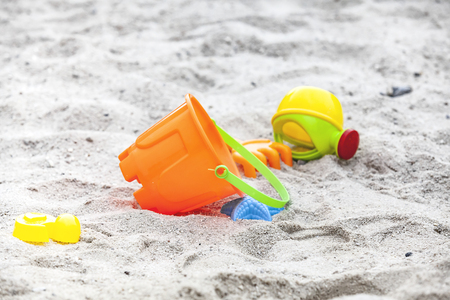 Set of colored plastic toys on a sand Stock Photo