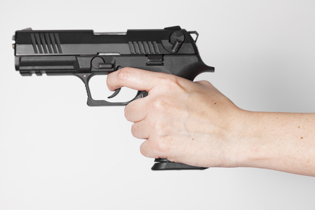 Hand holding a gun on white background Stock Photo