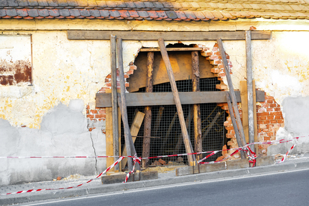 Big hole on the broken wall of a damage house after the car accident