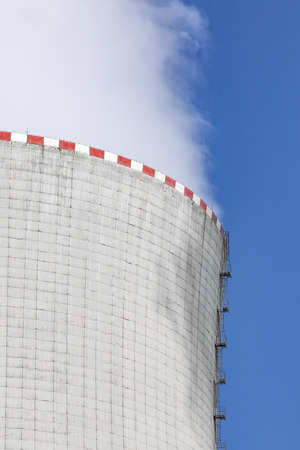 Steam going out of a cooling tower of a nuclear power plant into a blue sky