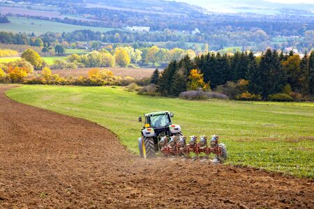 Tractor plowing the field. Autumn landscape.
