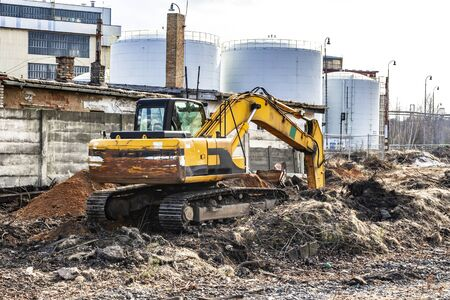 A yellow excavator in the construction site