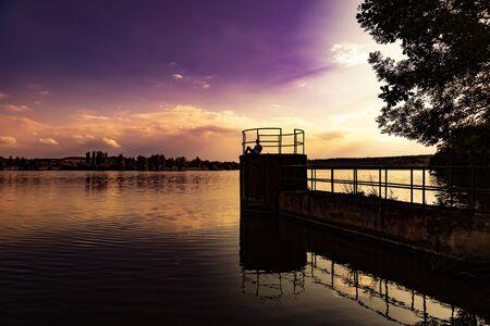 Young man relaxing at lake at sunset