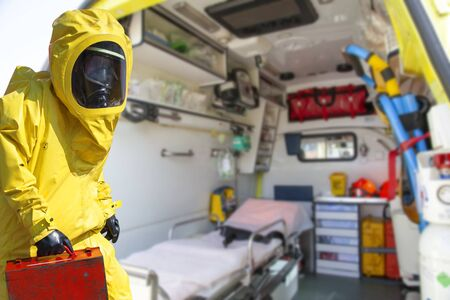 Ambulance and equipment in yellow protective hazmat suit. Epidemic virus.