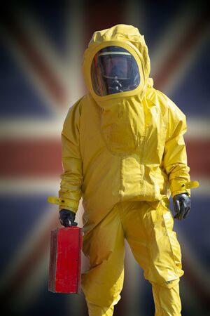 Isolated man holding briefcase in yellow protective hazmat suit. Flag of United Kingdom in background. Epidemic virus.