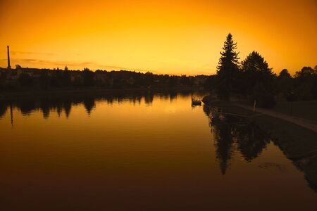 Landscape with river in front flowing at sunset sky Stock Photo - 147791554