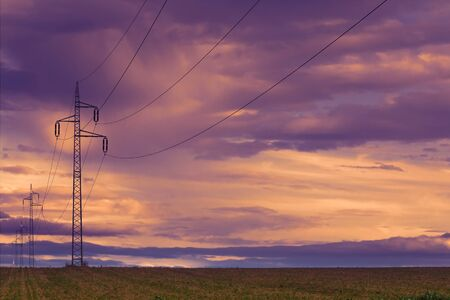 Power line and field at sunset sky. Autumn landscape.