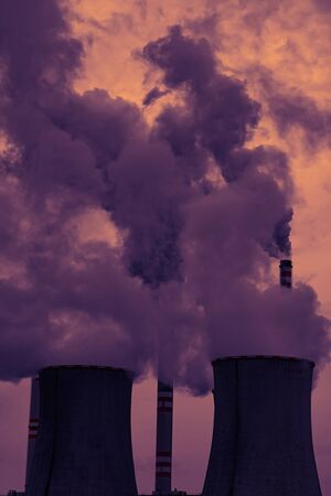 View of smoking coal power plant at sunset Stock Photo