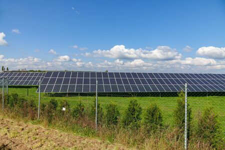 Solar energy panels on green field, blue sky