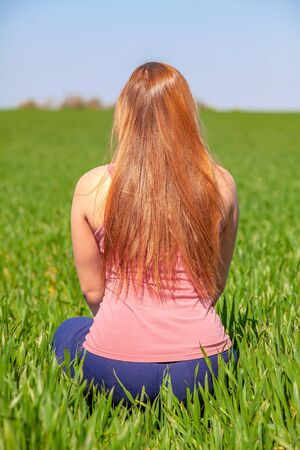 Happy woman in pink shirt enjoying in nature. Girl sitting on the grass, rest, relaxation. Stock Photo