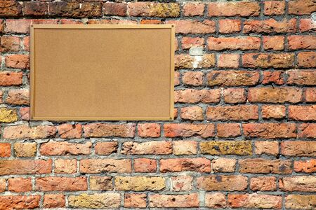 Cork noticeboard with wooden frame on brick wall Stock Photo