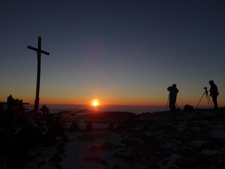 inversion: Silhouette of photograph is taking some photograph on mountain. A Crucifix In Front Of A Sky. Stock Photo