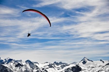 parapente: Paracaidista en las montañas de los Alpes