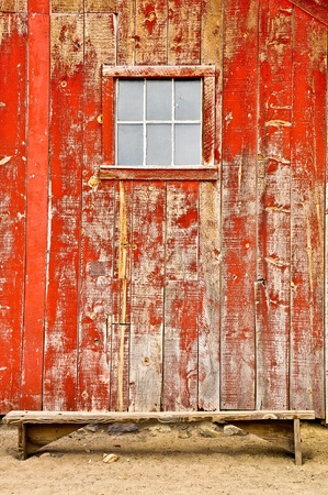 Red wood barn with window and bench Stock Photo