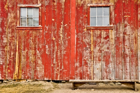 Red wood barn with windows and bench photo