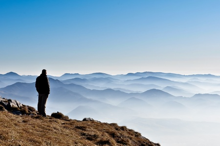Misty mountain hills and man silhouette photo