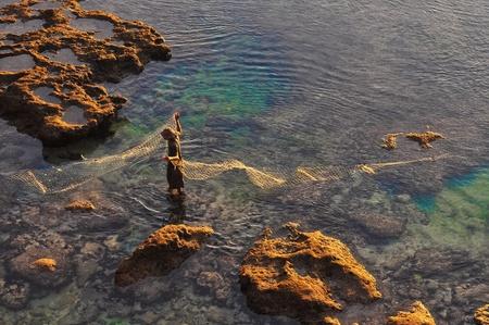 Fisherman at the sea coast with fishing net photo